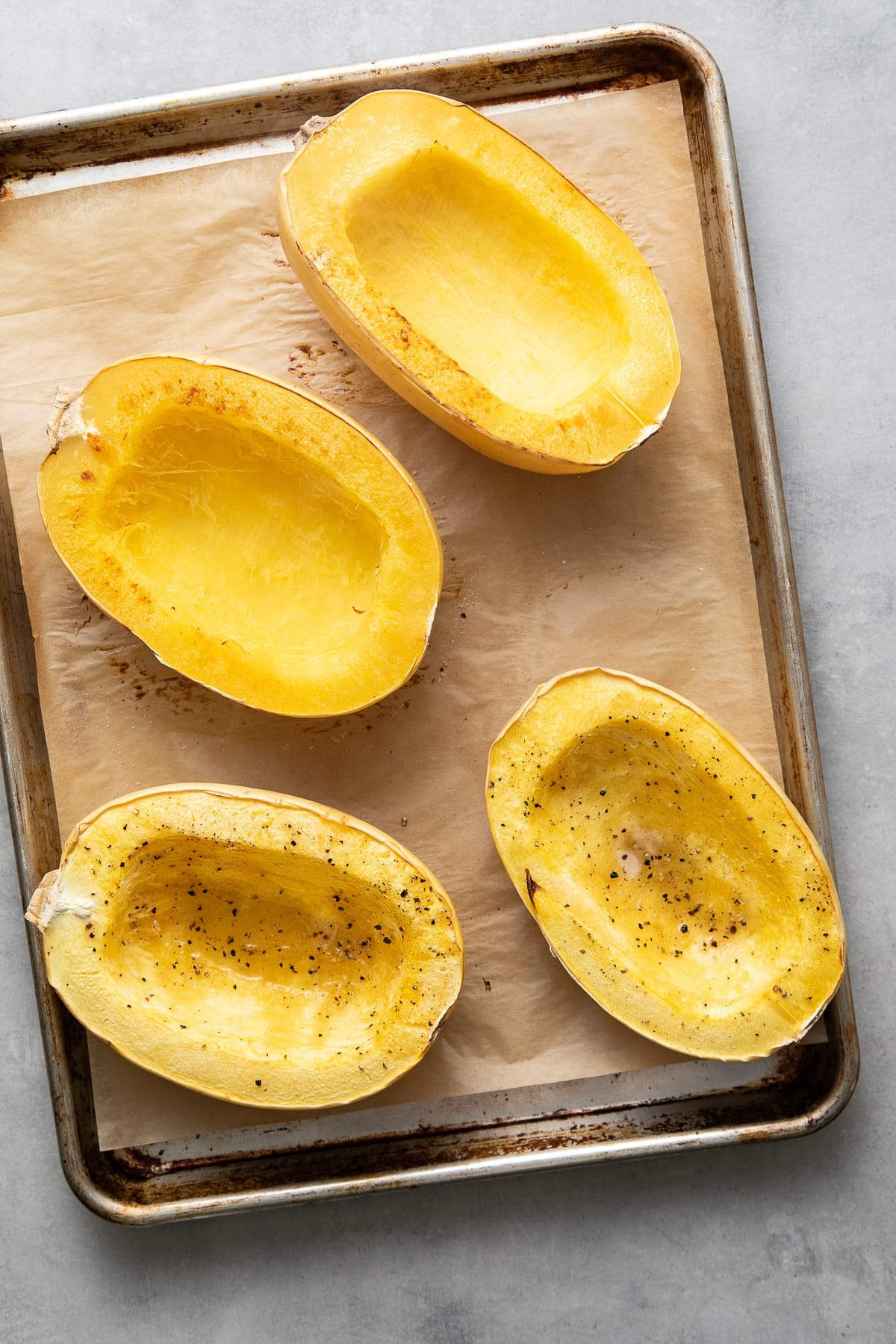 top down view showing freshly made spaghetti squash cooked 2 ways on a baking sheet.