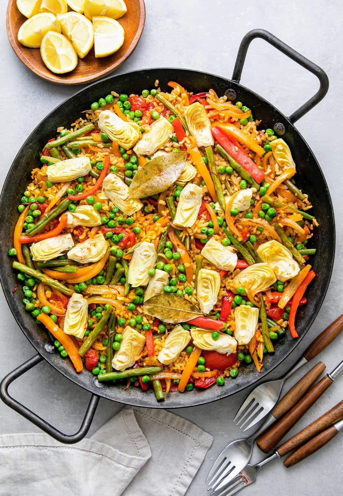 top down view of vegetable vegan paella in a paella pan with items surrounding.