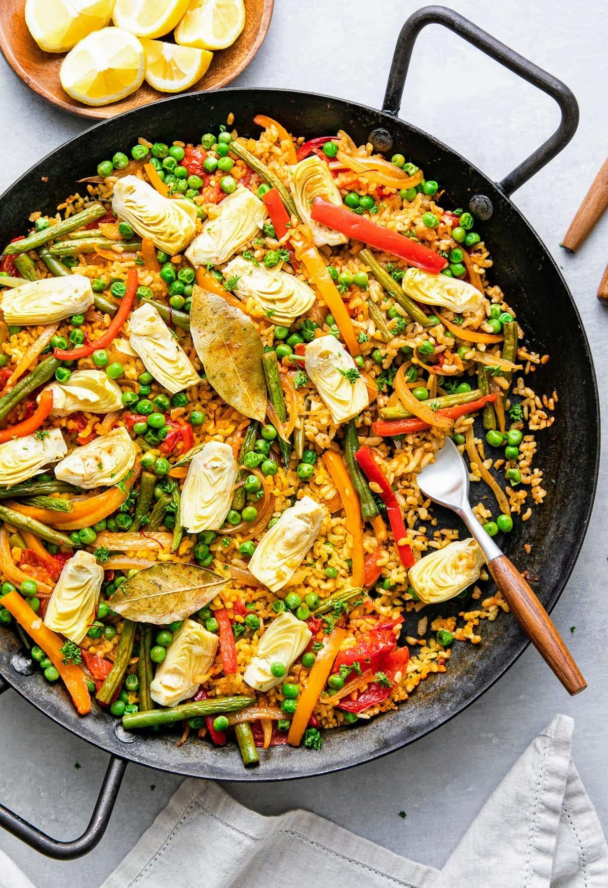 top down view of vegetable vegan paella in a paella pan with fork and items surrounding.