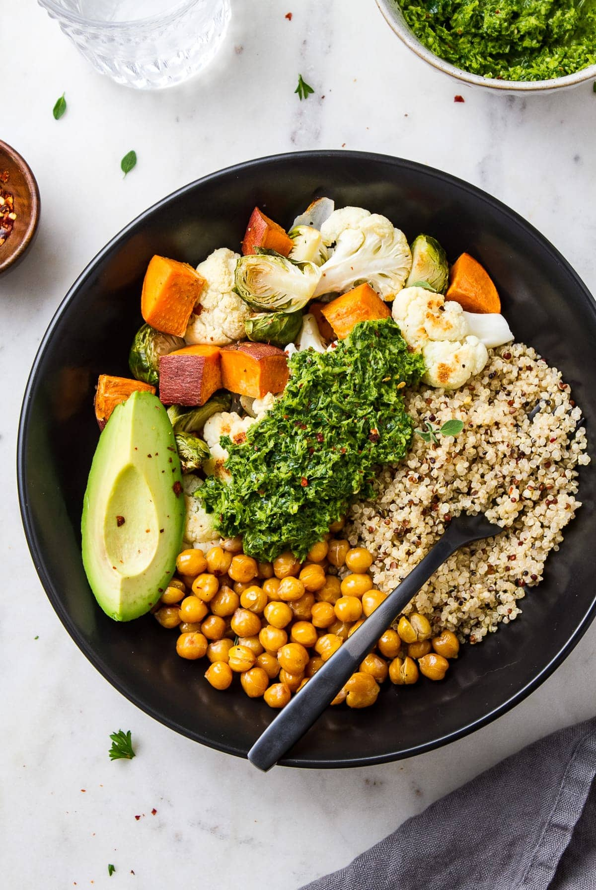 top down view of a black bowl with roasted veggies, chickpeas quinoa and chimichurri making a chimichurri nourish bowl.