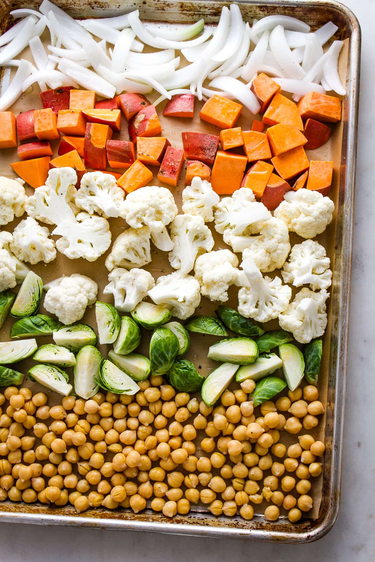 top down view of prepped nourish bowl veggies on a baking sheet before being roasted.