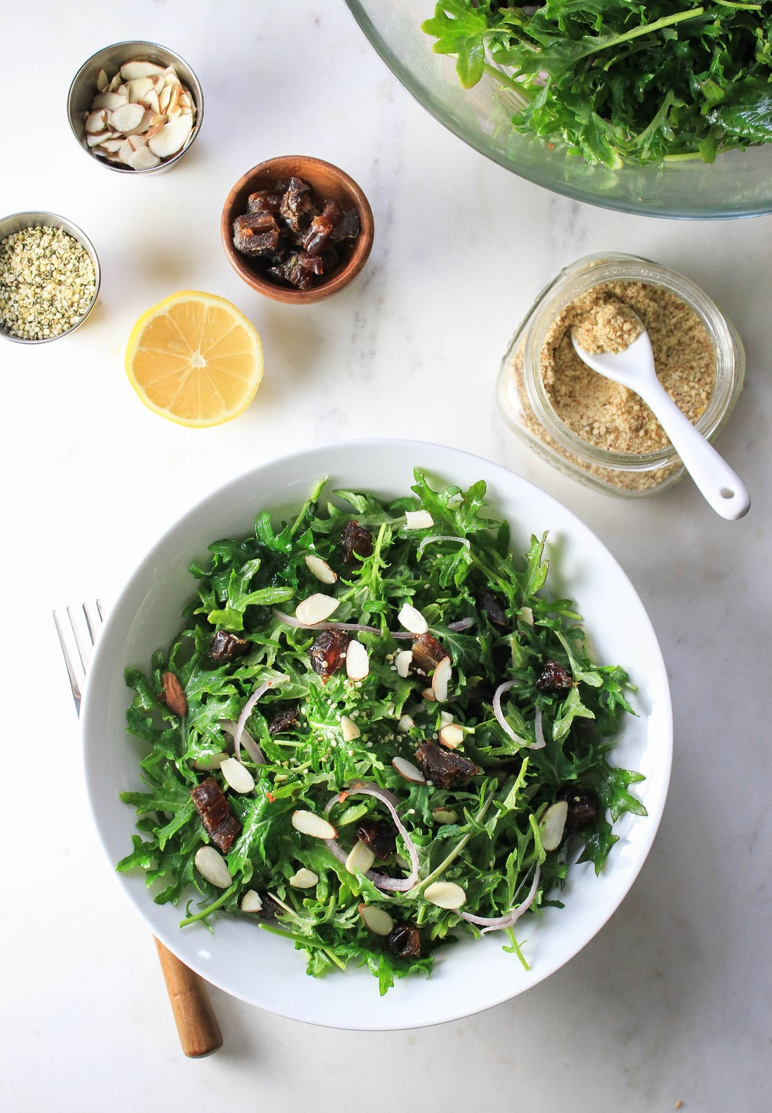 top down view of kale salad with dates, almonds and lemon dressing in a white serving bowl.