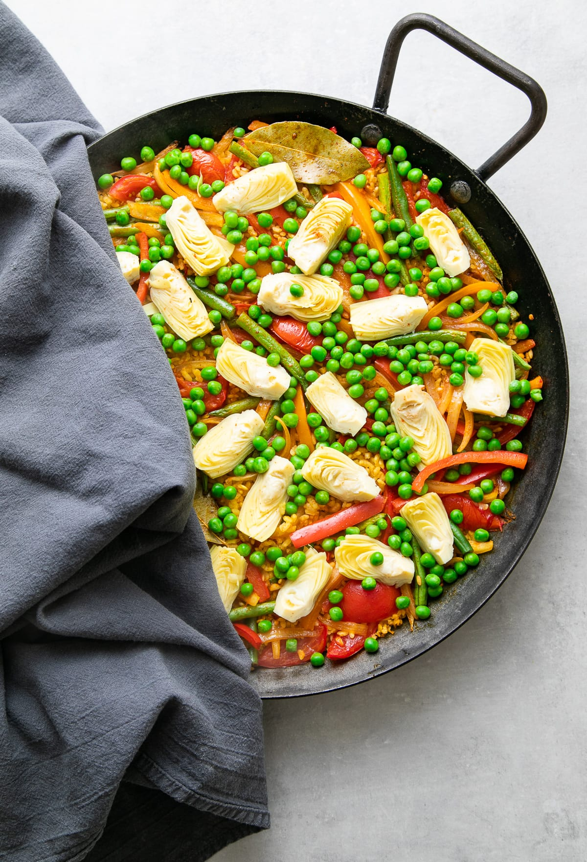 top down view showing veg broth poured over rice and veggies in paella pan.
