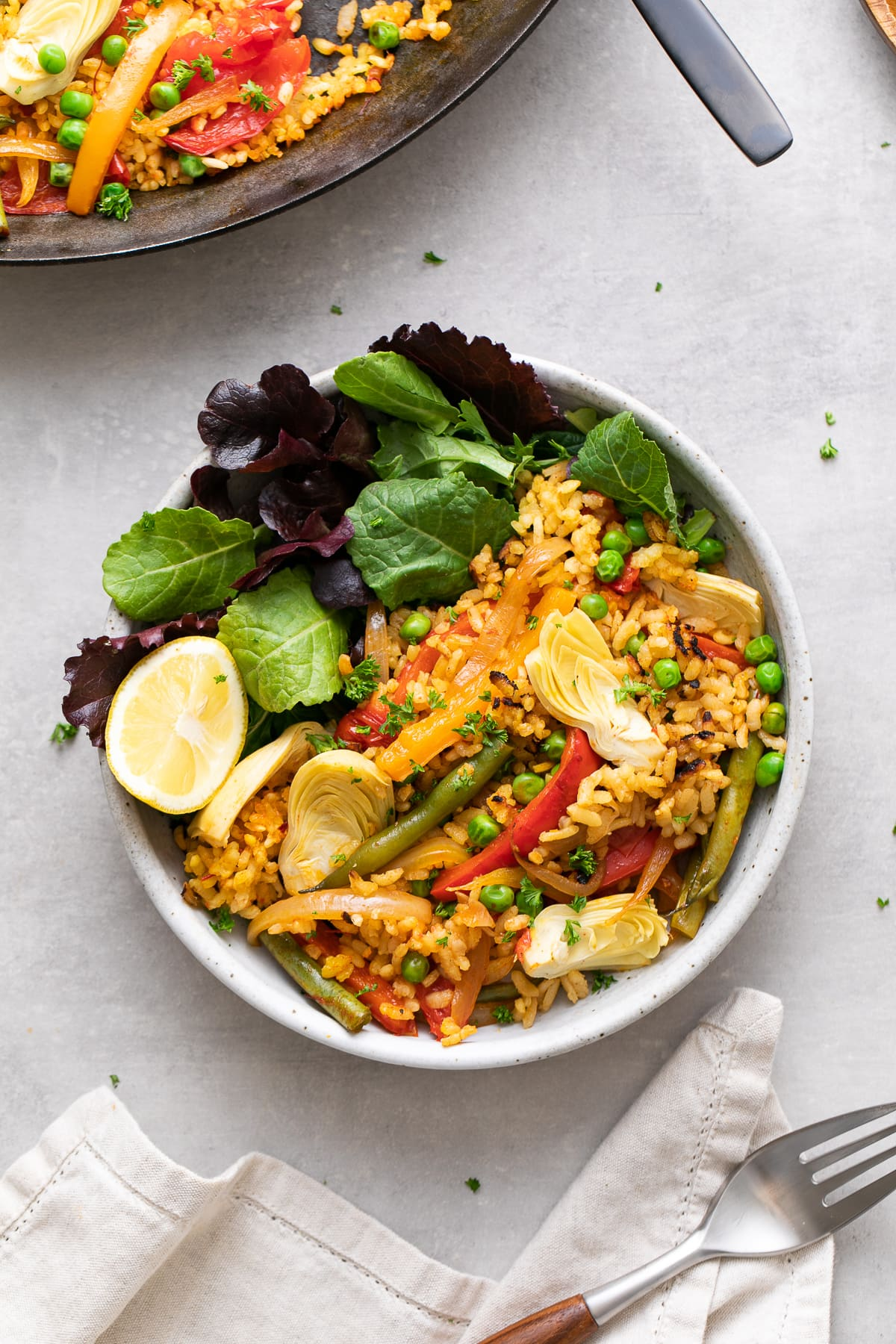 top down view of bowl with leafy greens topped with serving of veggie vegan paella.
