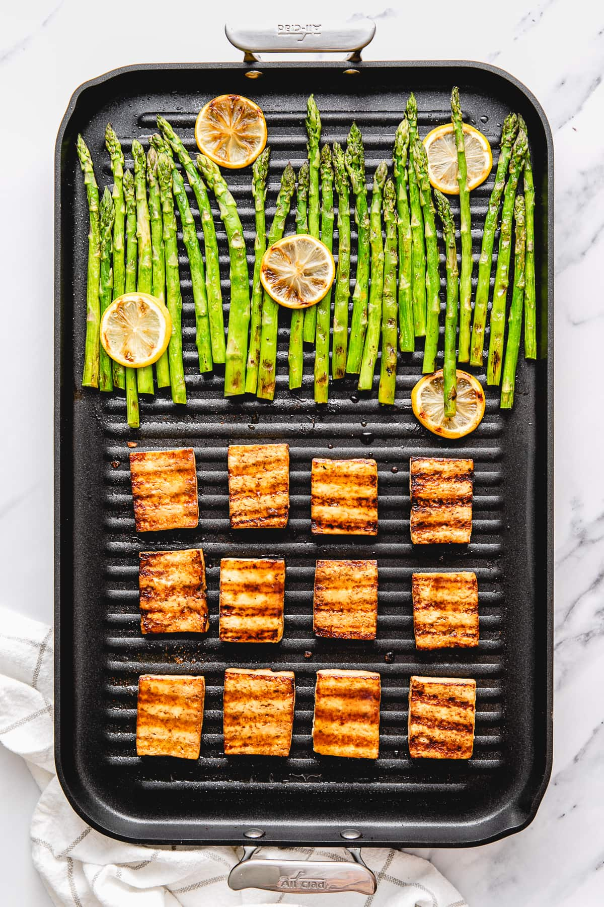 top down view of pan grilled tofu and asparagus on a nonstick grill.