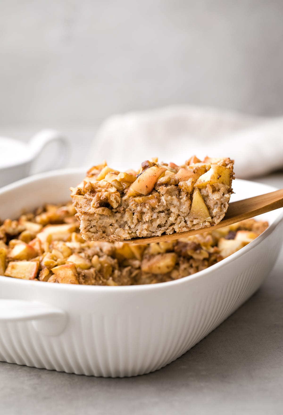 head on view of slice of apple baked oatmeal on wooden spatula.