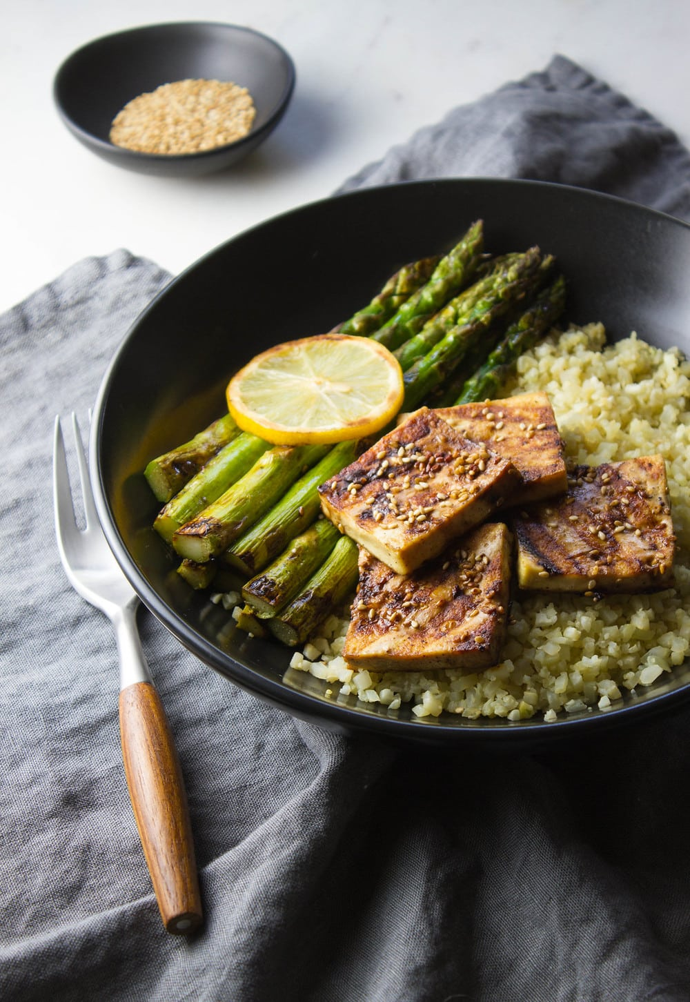 grilled tofu and asparagus with ginger cauliflower rice served in a black bowl