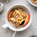 top down down of healthy apple baked oatmeal in a bowl with spoon and items surrounding.