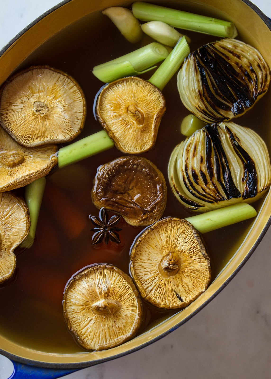 top down view showing the process of making vegan pho broth in a dutch oven.