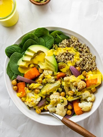 top down view of roasted cauliflower and sweet potato nourish bowl drizzled with turmeric tahini dressing.