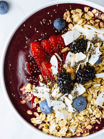 up close, top down view of an acai bowl topped with granola and various fresh fruits.