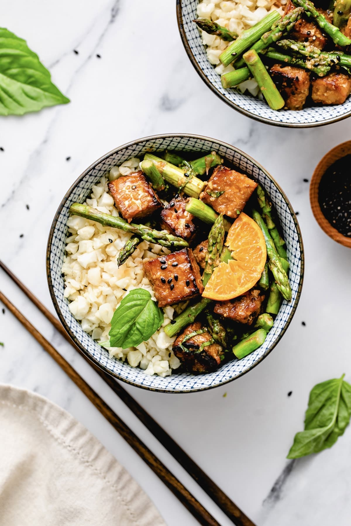 top down view of bowl of orange tempeh and asparagus with cauliflower rice.
