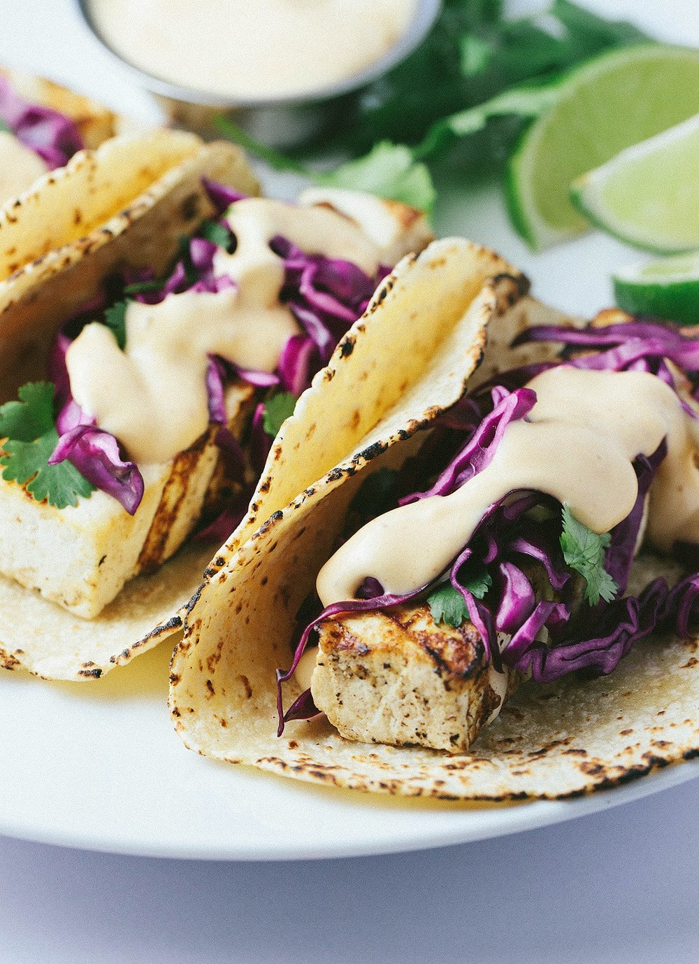 side angle view of grilled tofu taco piled high with red cabbage slaw and spicy sauce