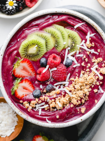 top down view of homemade acai bowl topped with healthy toppings with items surrounding.