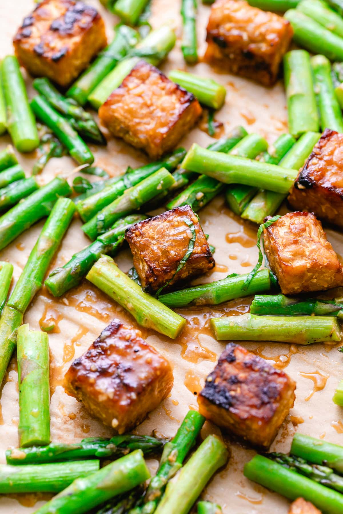 side angle view of baking sheet with fresh roasted orange miso tempeh and asparagus.