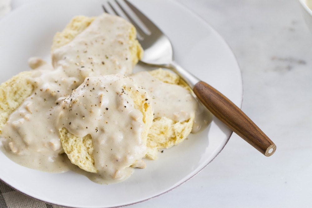 up close, side angle view of vegan biscuits smothered with gravy on a small with plate with fork with wooden handle.