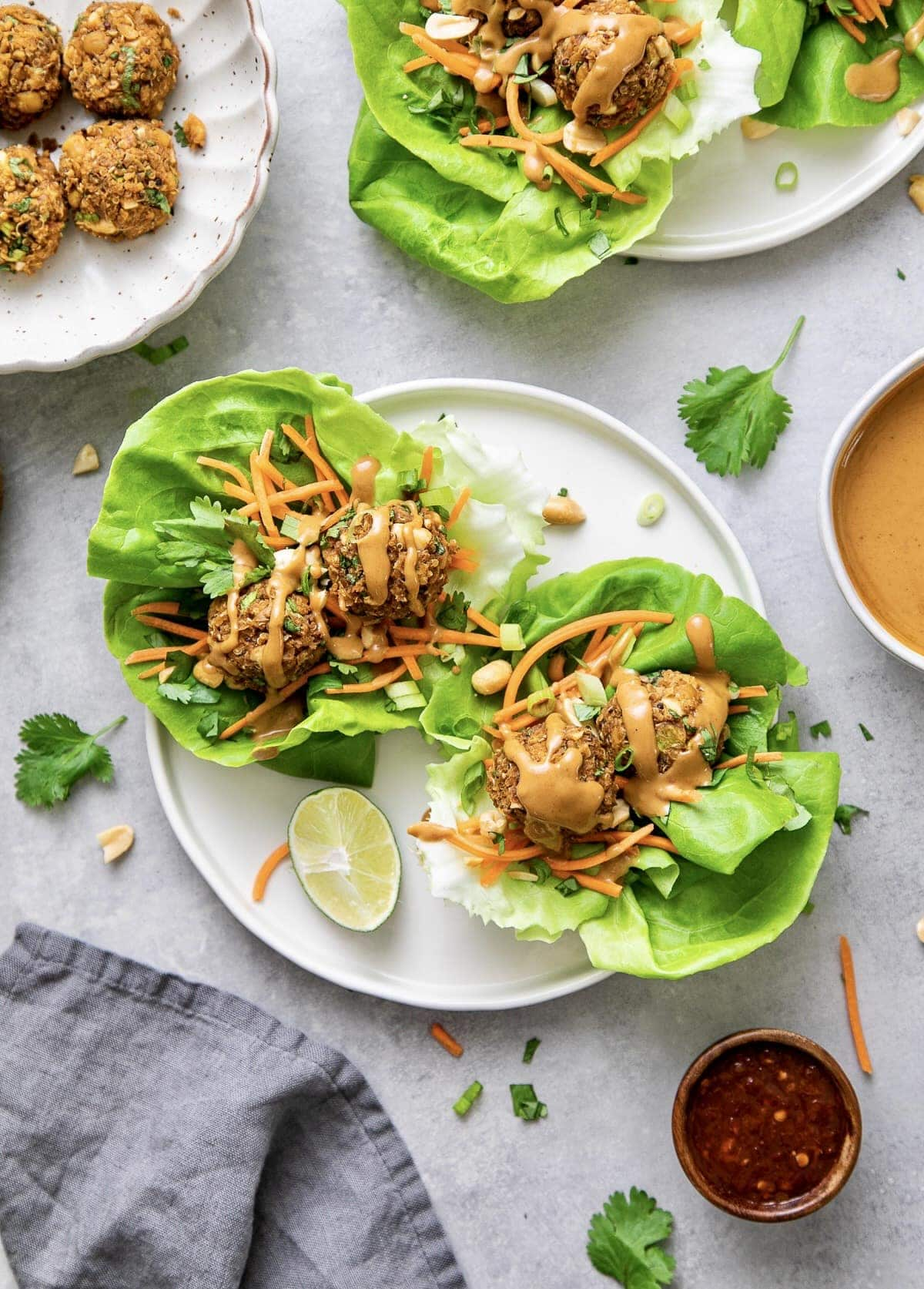 top down view of vegan lettuce wraps with thai quinoa meatballs on a plate with items surrounding.