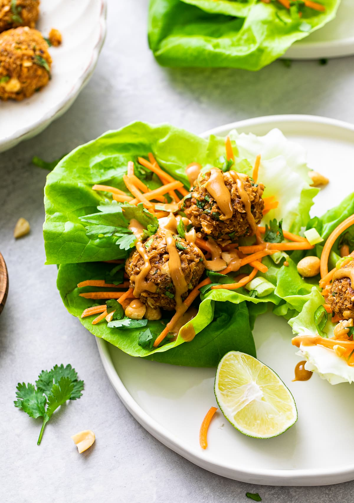 side angle view of vegan lettuce wraps with thai quinoa meatballs on a plate with items surrounding.