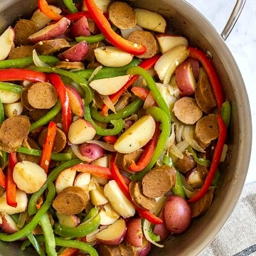 a pan with cooked sausage, peppers, potatoes and onion