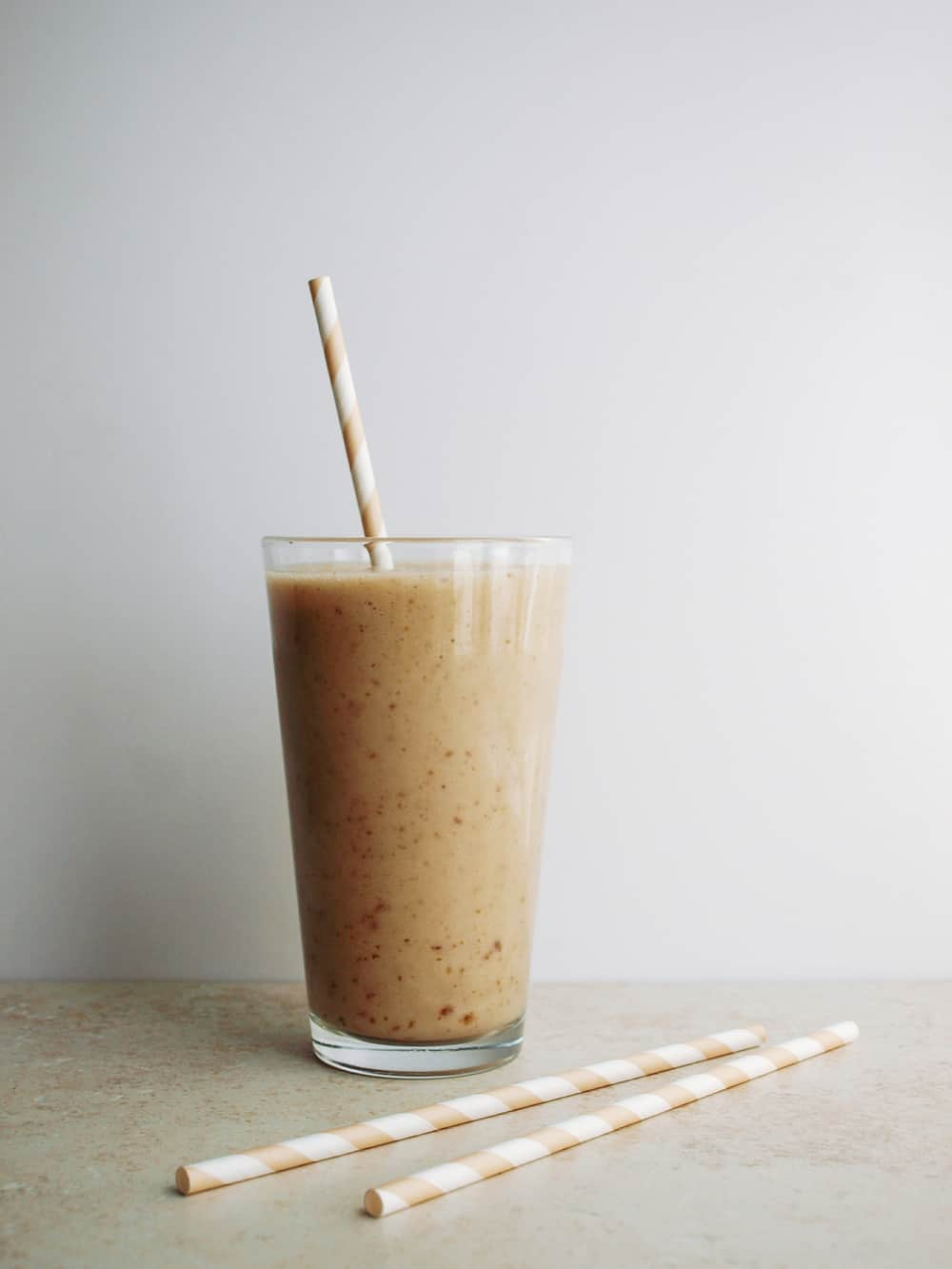 vanilla date smoothie in glass with straw