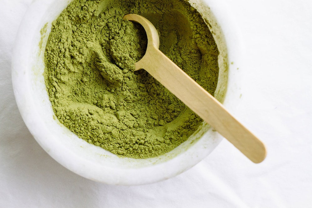 top down view of matcha powder in a small marble bowl with wooden spoon.