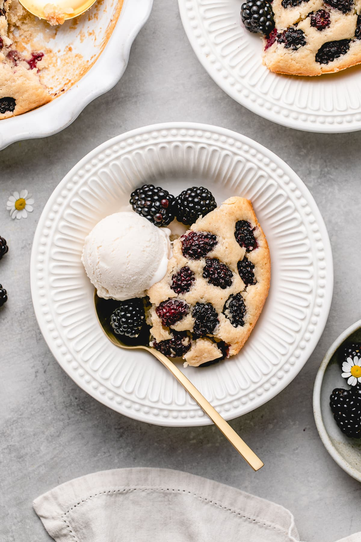top down view of plated vegan blackberry cobbler in a bowl with scoop of ice cream.