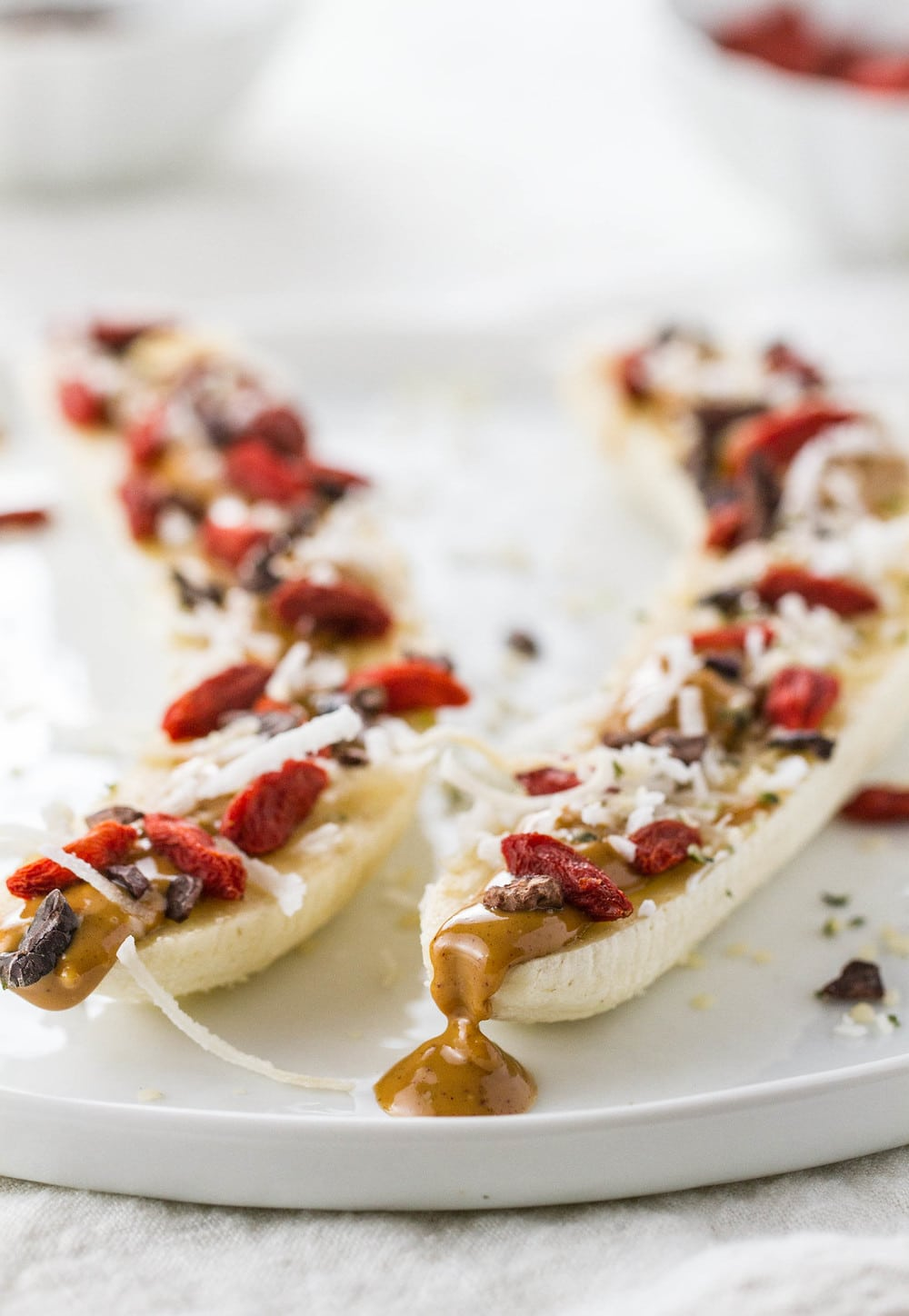 side angle view of loaded banana boats on a white plate.