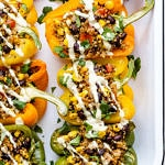 top down view of quinoa stuffed colored bell peppers on a serving dish topped with vegan cashew cheese sauce.