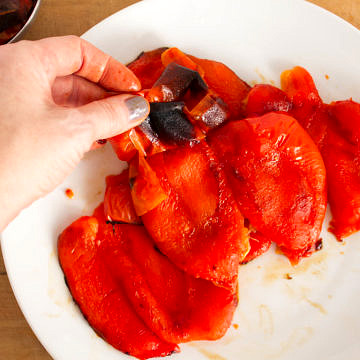 top down view of the skin of roasted red pepper being peeled from the flesh of steamed red pepper.