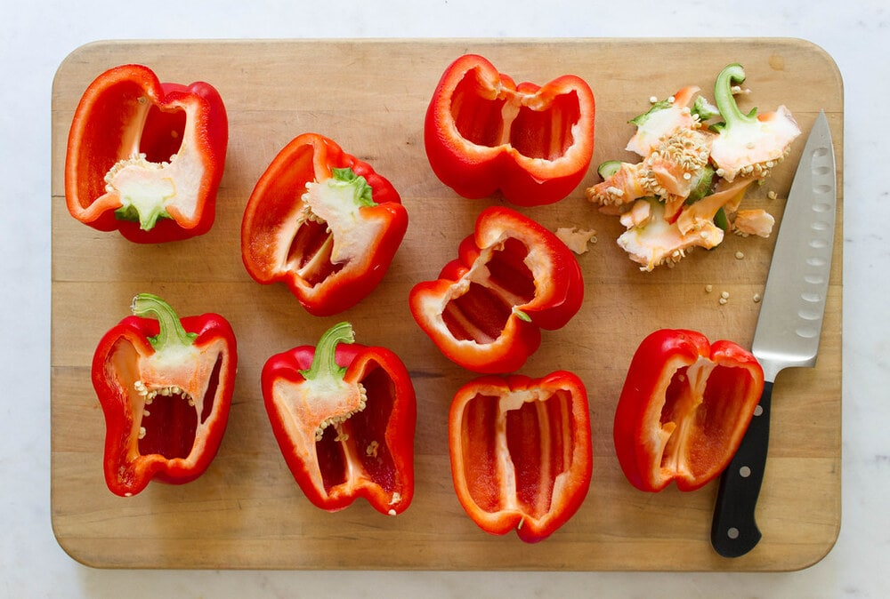 top down view of red bell peppers, cored, seeded and sliced in half lengthwise on a wooden cutting board.