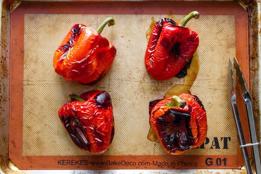 top down view of freshly roasted whole red peppers on a rimmed baking sheet.