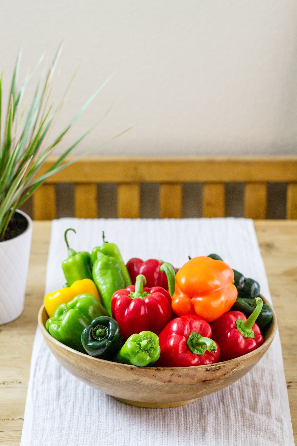 a variety of pepper in a wooden bowl on a table.