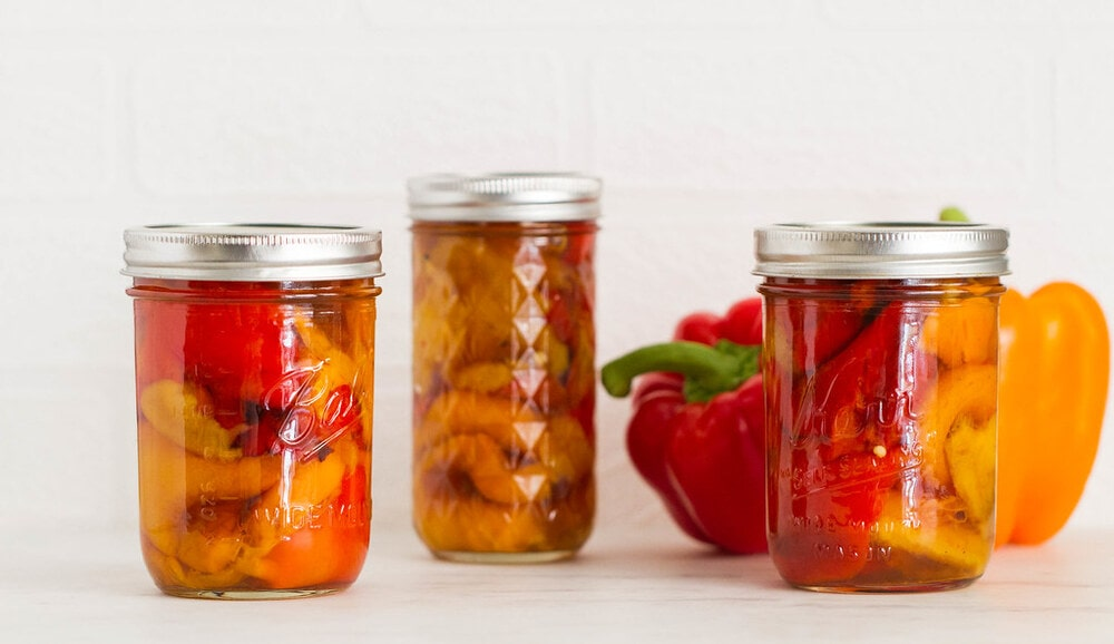 head on view of roasted red peppers in mason jars.