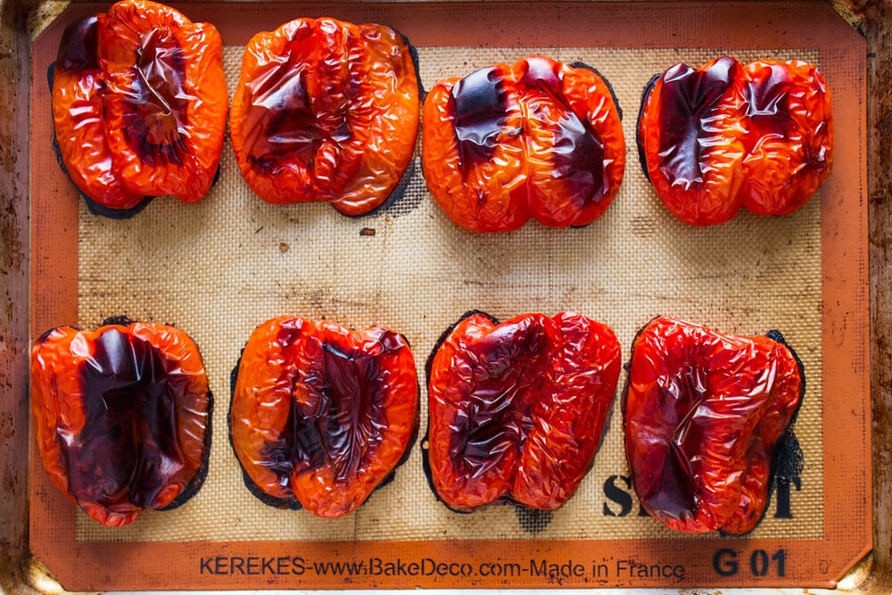 top down view of freshly oven sliced roasted red peppers on a rimmed baking sheet.