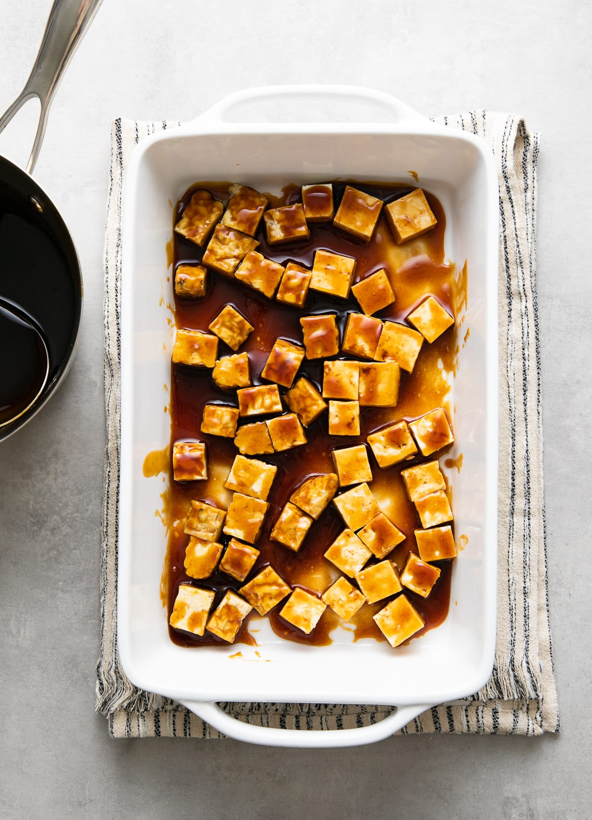 top down view of cubed tofu and tempeh mixed with teriyaki sauce before baking.