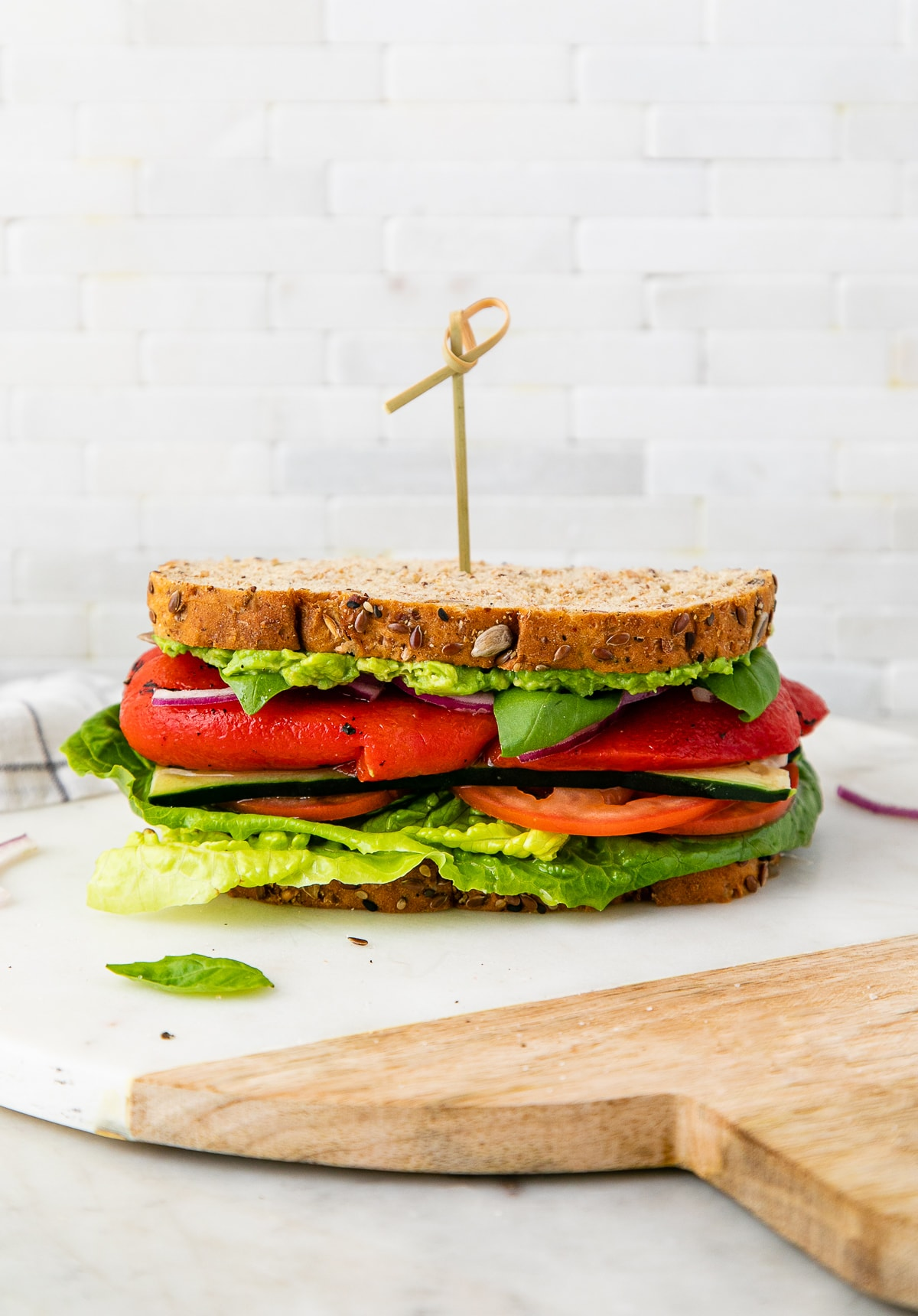head on view of healthy mediterranean veggie sandwich with red peppers on a marble serving tray.