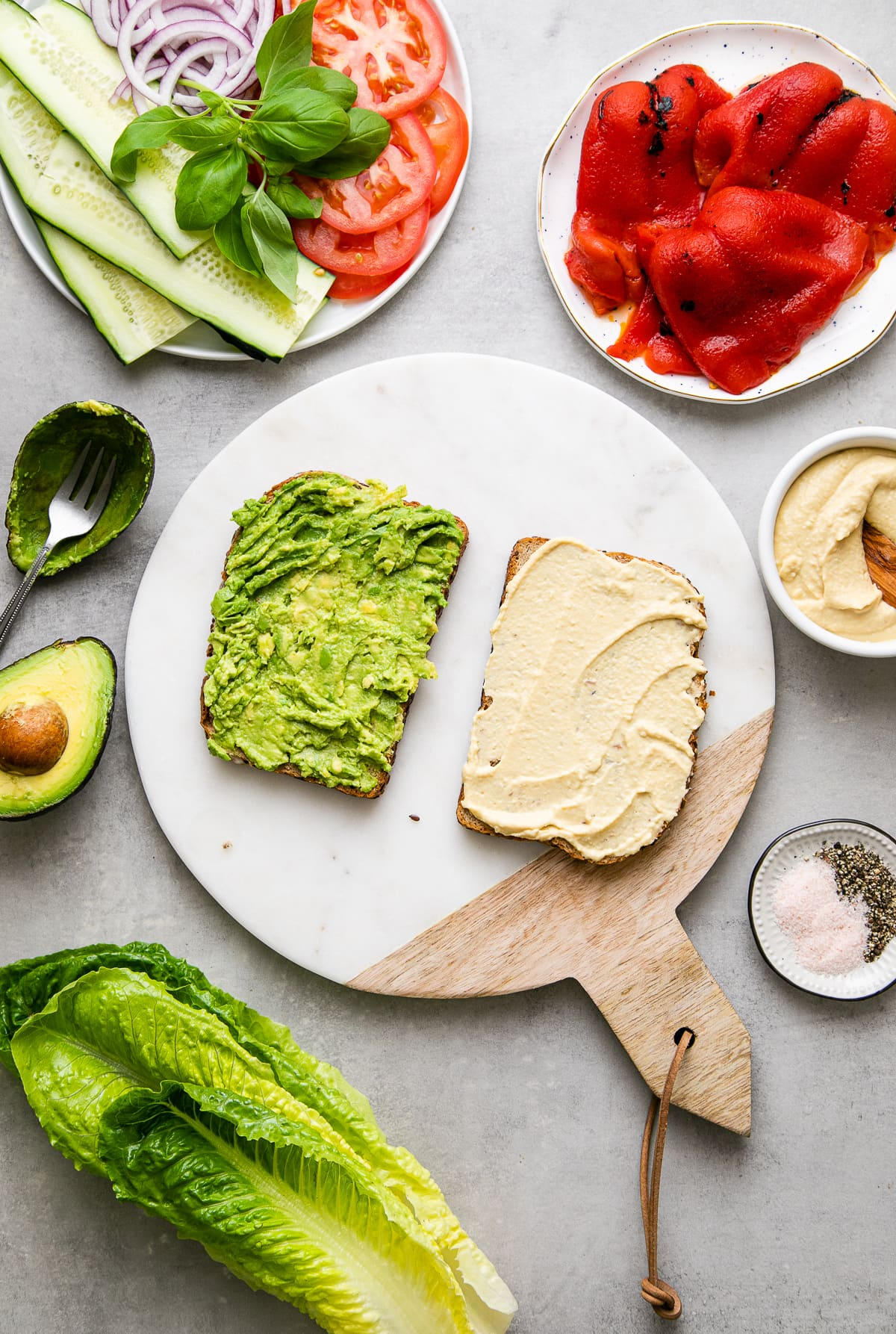 top down view showing the process of layer avocado and hummus on bread slices with items surrounding.