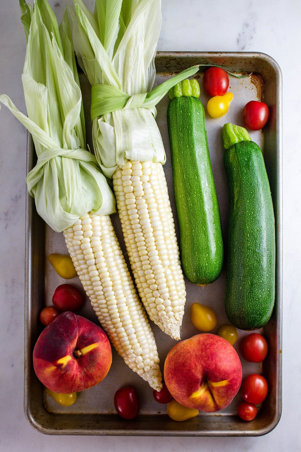 top down view of produce on a rimmed baking sheet.