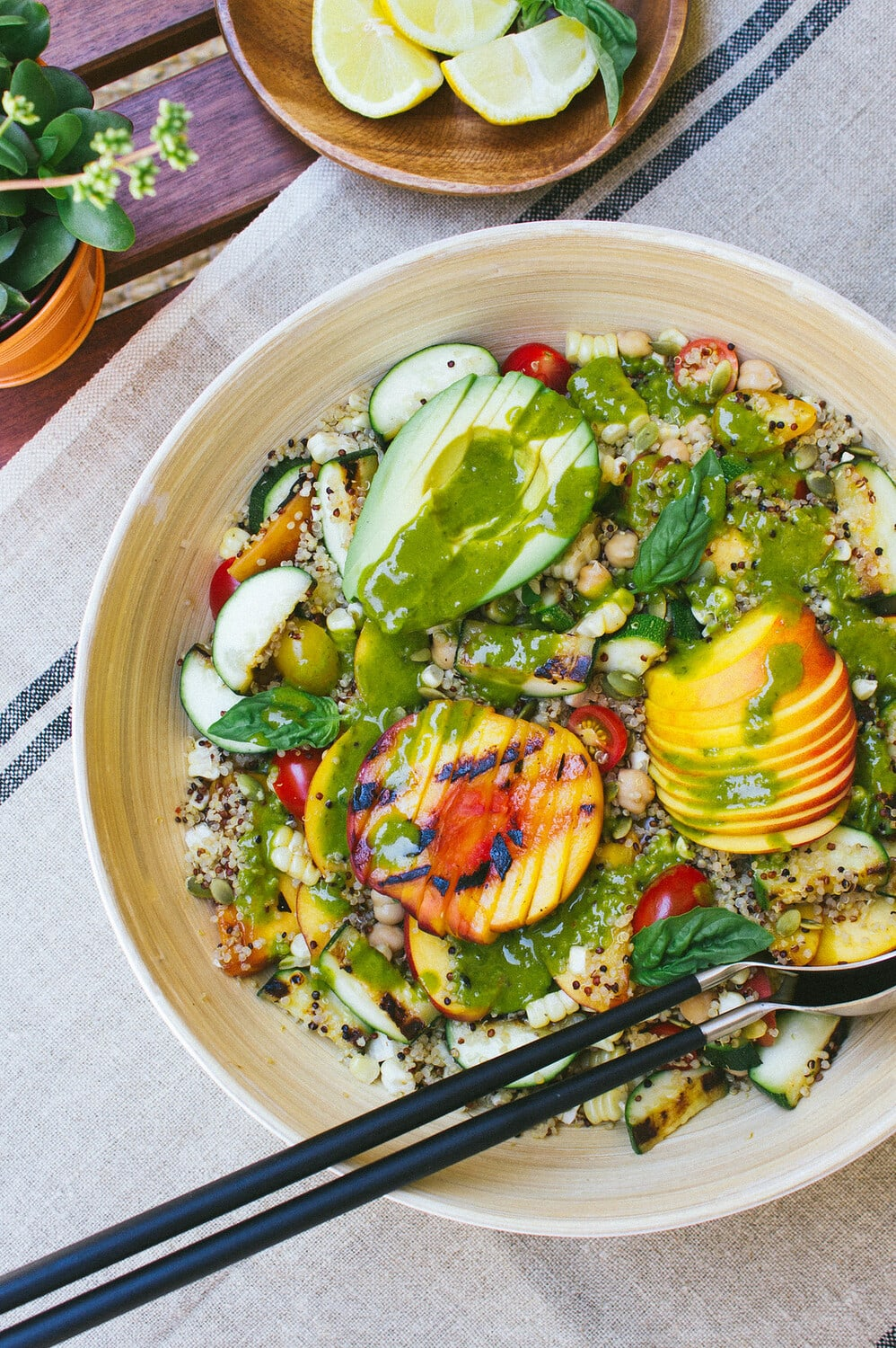 top down view of grilled peach, corn and zucchini quinoa salad with basil dressing poured over top.