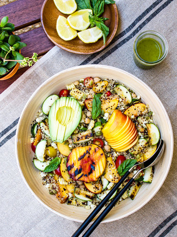 top down view of grilled peach, corn and zucchini quinoa salad in a large mixing bowl before the dressing is added.