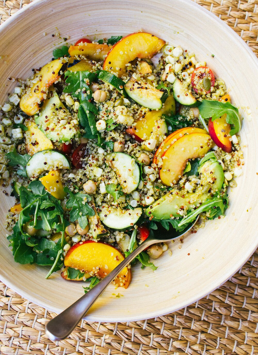top down view of grilled peach, corn and zucchini quinoa salad mixed together in a mixing bowl.