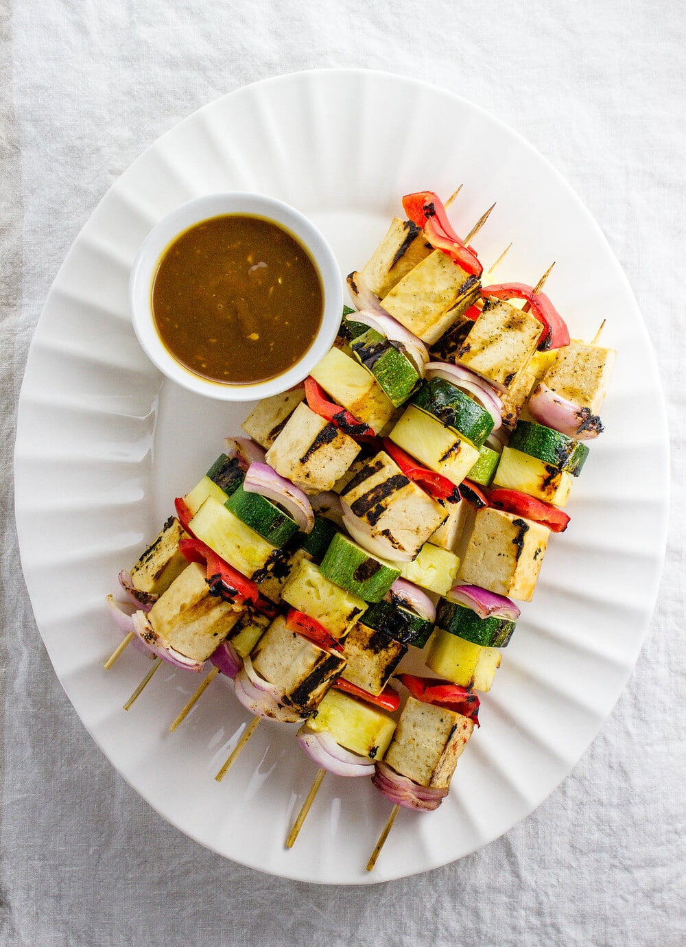 top down view of a serving platter with 6 grilled tofu skewers.