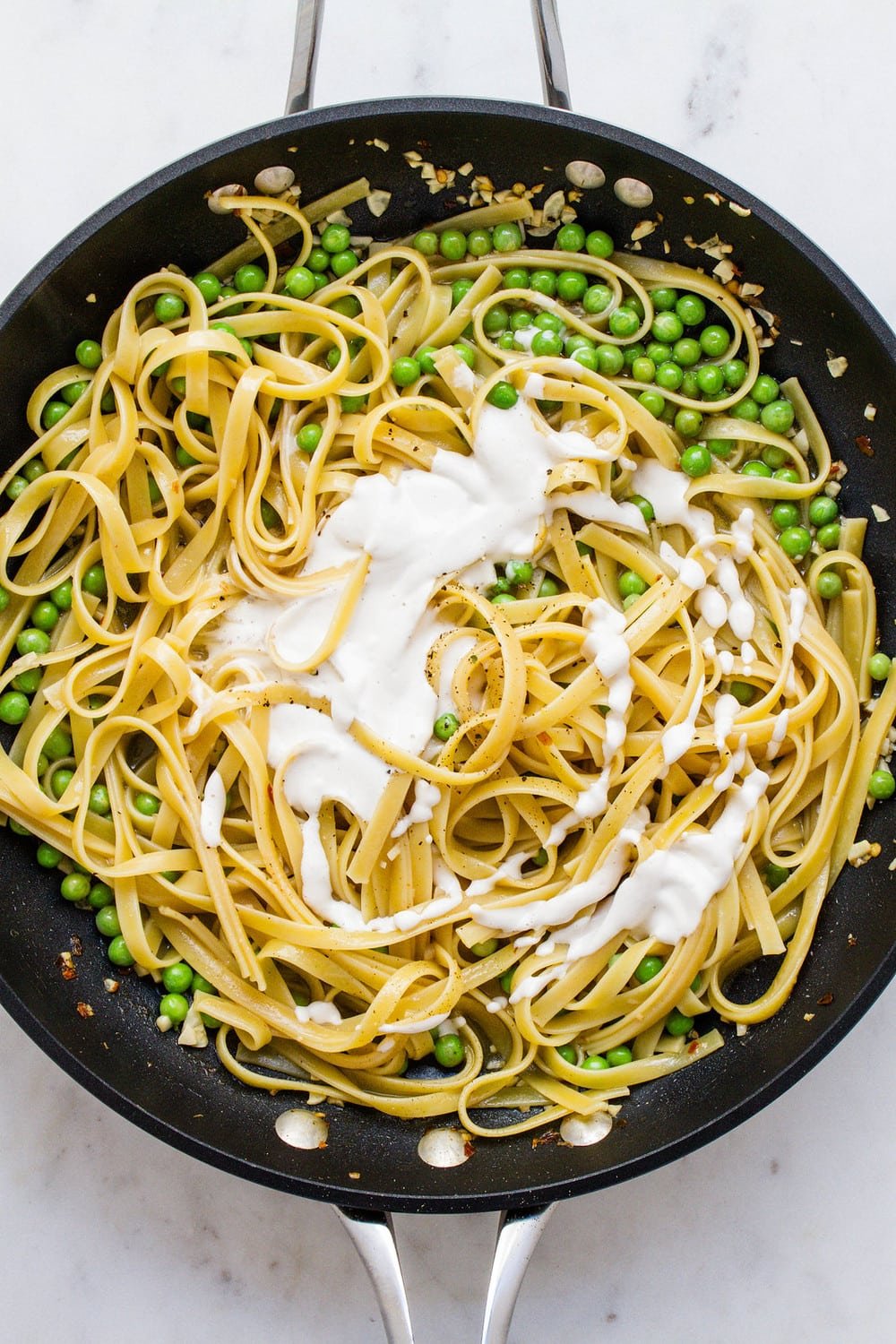 top down view of skillet with fettuccine noodles, cashew alfredo sauce, and peas ready to be mixed