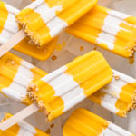 top down view of coconut mango popsicles arranged on tray with ice.