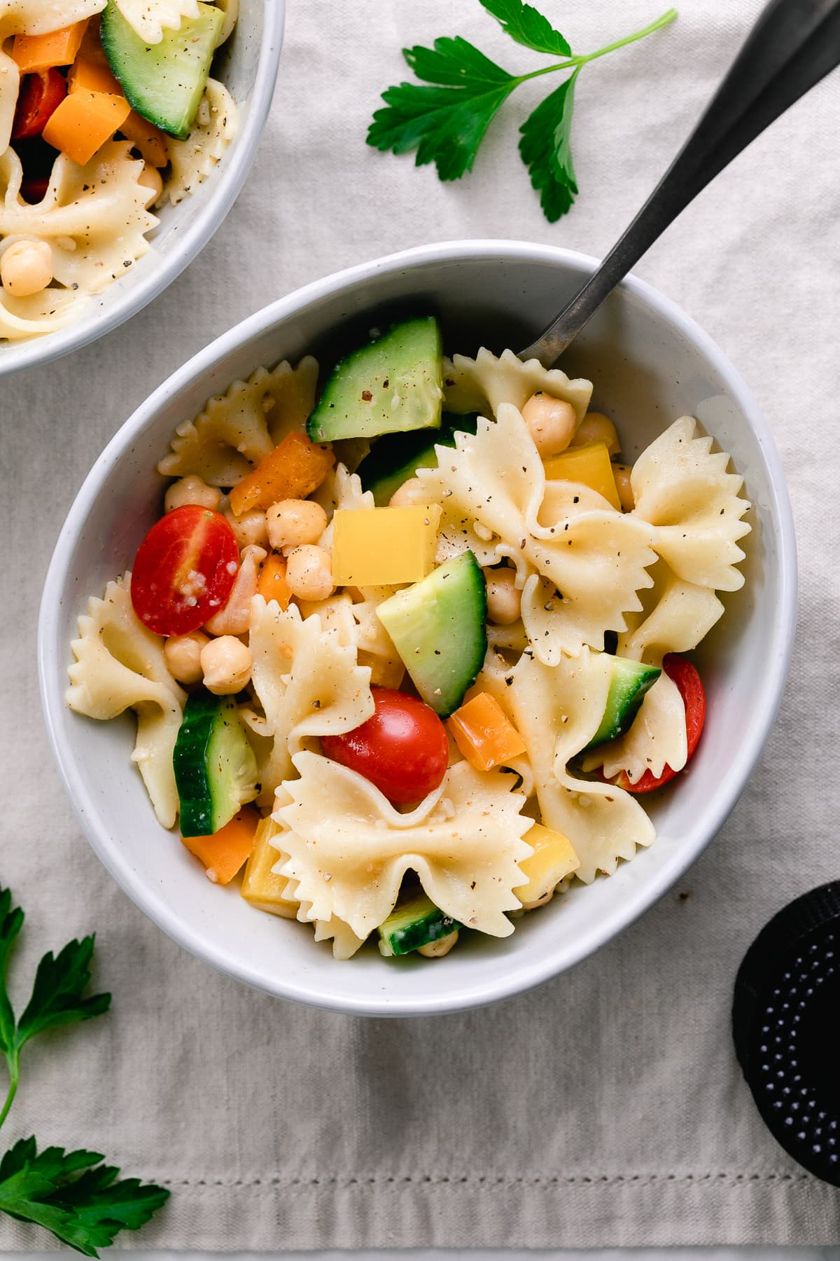top down view of healthy pasta salad in a bowl with items surronding.