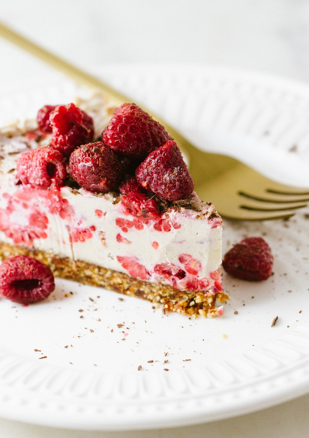 side angle view of a slice of vegan no bake raspberry vanilla cheesecake on a white plate with gold fork.