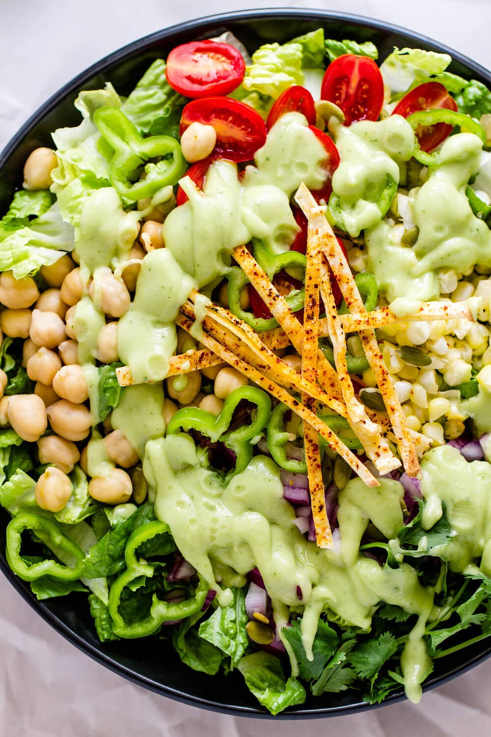 up close, top down view of healthy southwest chickpea salad drizzled with creamy lime avocado dressing.