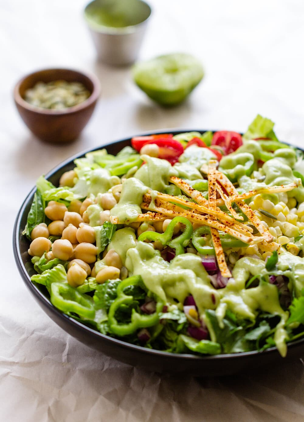 side angle view of healthy southwest chickpea salad drizzled with creamy lime avocado dressing.