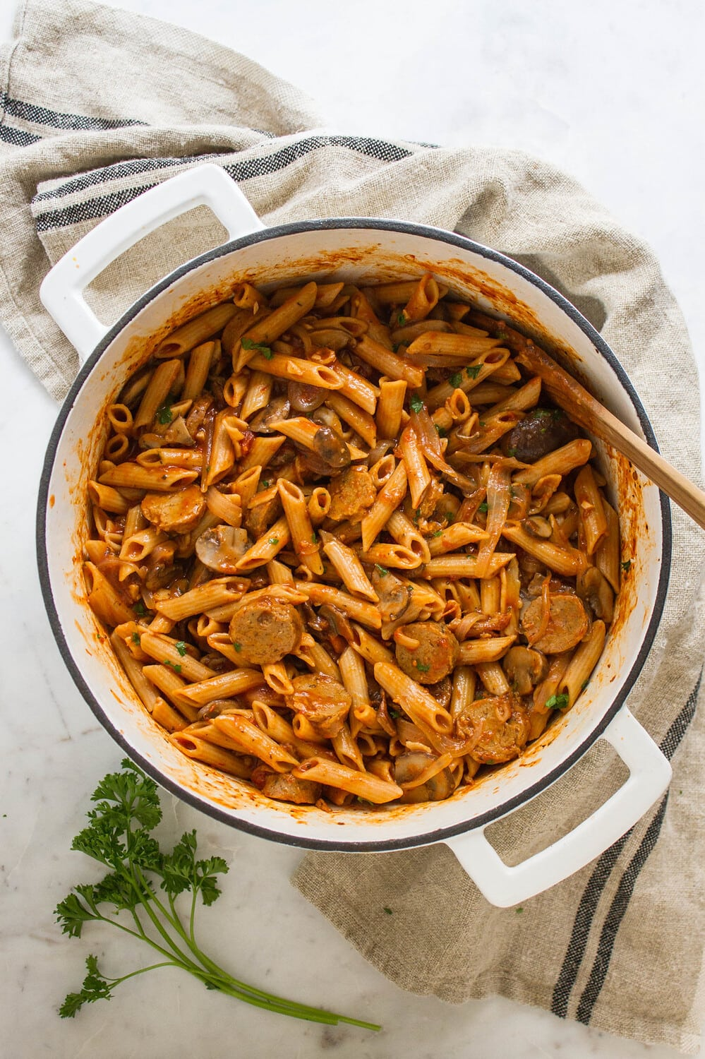 top down view of one pot penne pasta with mushrooms and sausage finished cooking in a white pot.