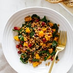 top down view of a serving of autumn wheat berry and butternut squash salad in a white bowl with gold fork.
